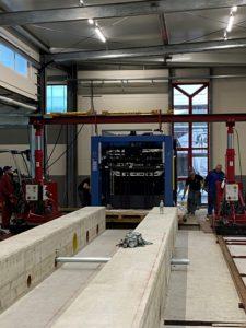 Blaue Druckmaschine bei HvC von vorne umrandet von roten Stahlbühnen vor einem Betonfundament