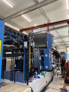 Blaue Druckmaschine von vorne auf Betonfundament bei HvC, oberhalb gesichert durch eine rote Stahlbühne