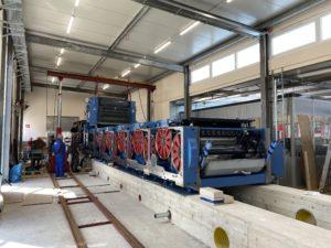 Blaue Druckmaschine von der hinteren Seite auf Betonfundament mit roter Walzenverkleidung in einer Produktionshalle von Hubert von Carnap