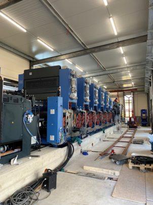 Blaue Druckmaschine von der Seite auf Betonfundament mit roter Walzenverkleidung in der Produktionshalle von Hubert von Carnap